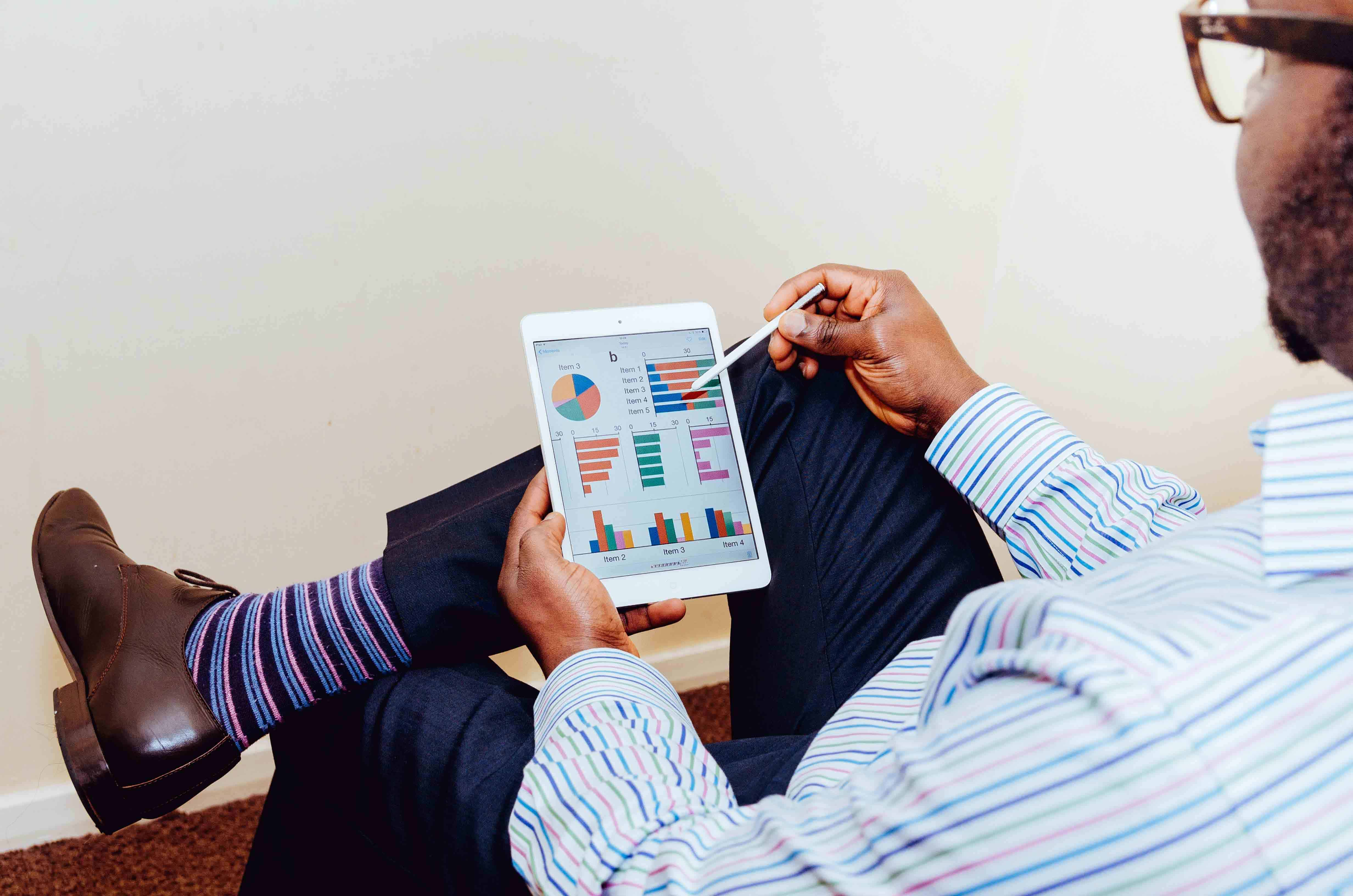 A man looking at analytics on an iPad - important digital advertising formulas - Sussex New Media 2019
