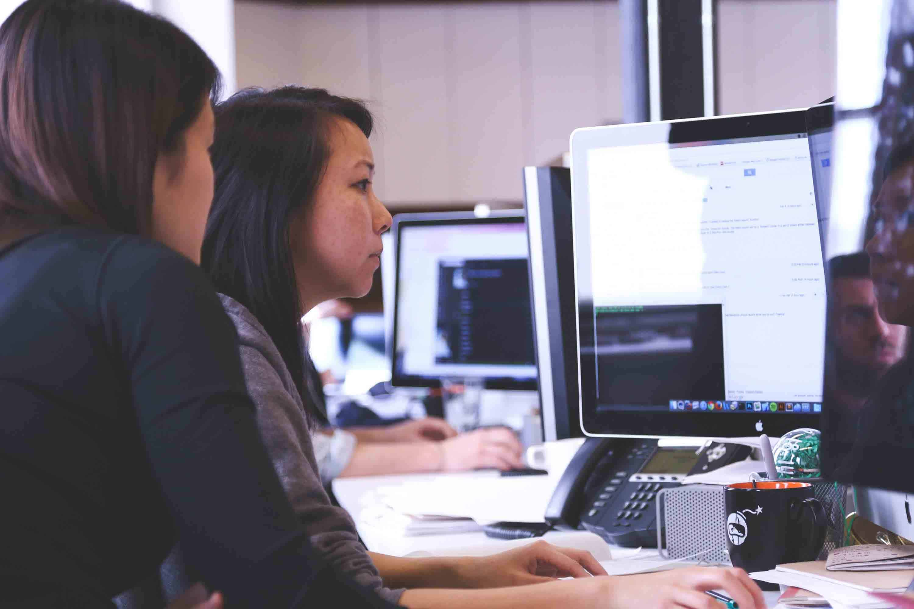 two women sitting in front of a computer screen using software to code